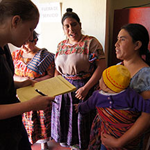 Maya interviews a client in Santa Clara la Laguna as her friends listen.