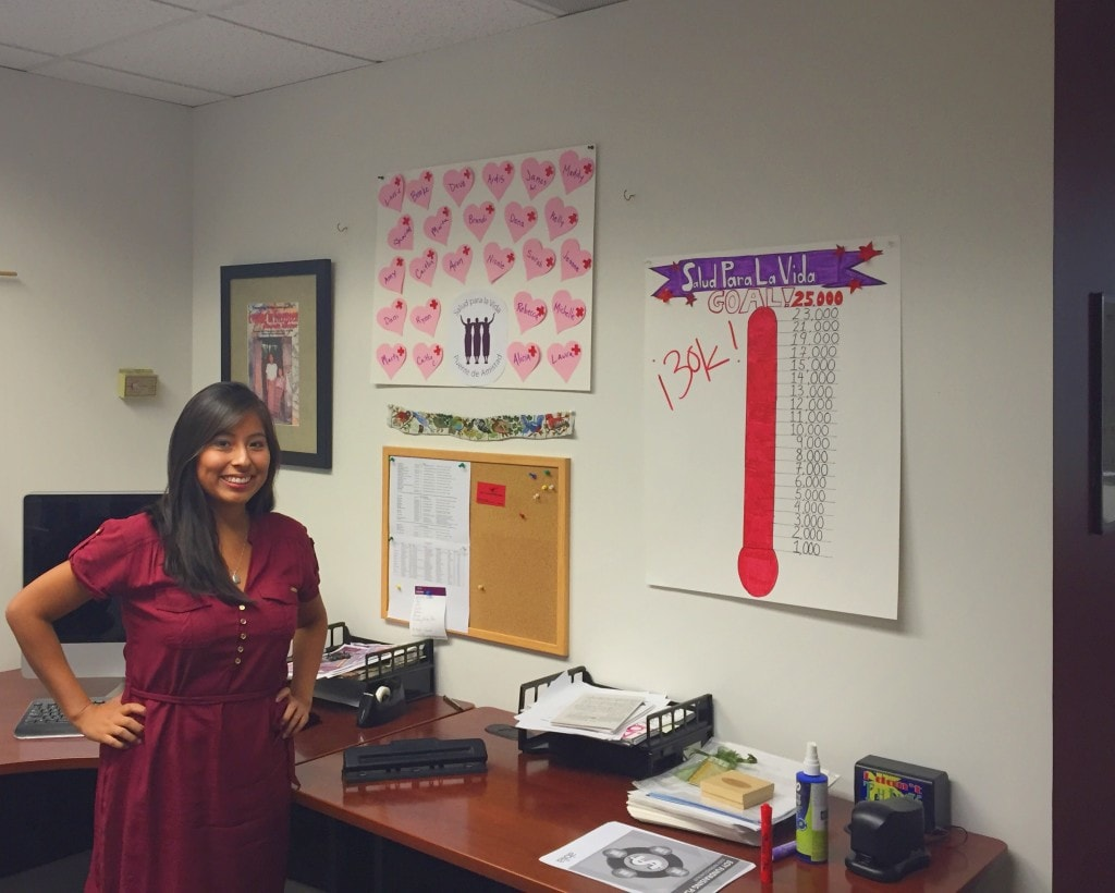 Marketing intern standing in front of a crowdfunding thermometer.