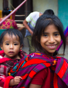 A daughter of a cooperative member totes around her little brother on her back, traditional in Guatemala.