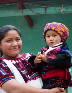 Tomasa, a member of Yolanda's cooperative, with her son. They are dressed in traje, which is the indigenous Mayan dress in Guatemala.
