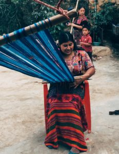 A member of Yolanda's cooperative weaves at her traditional backstrap loom.